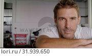 Купить «Male mechanic standing in motorbike repair garage 4k», видеоролик № 31939650, снято 10 февраля 2019 г. (c) Wavebreak Media / Фотобанк Лори