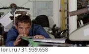 Купить «Male mechanic repairing motorbike in repair garage 4k», видеоролик № 31939658, снято 10 февраля 2019 г. (c) Wavebreak Media / Фотобанк Лори