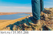 Купить «Men's legs in sneakers and jeans stand on a rock against the background of a lake and a blue sky.», фото № 31951266, снято 23 апреля 2019 г. (c) Акиньшин Владимир / Фотобанк Лори