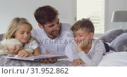 Купить «Father with his children reading story book in bedroom at home 4k», видеоролик № 31952862, снято 12 марта 2019 г. (c) Wavebreak Media / Фотобанк Лори