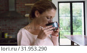 Купить «Woman drinking coffee in kitchen at comfortable home 4k», видеоролик № 31953290, снято 12 марта 2019 г. (c) Wavebreak Media / Фотобанк Лори