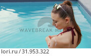 Купить «Woman in bikini applying sunscreen lotion on her body near poolside 4k», видеоролик № 31953322, снято 12 марта 2019 г. (c) Wavebreak Media / Фотобанк Лори