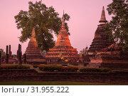 Три ступы на руинах  буддистского храма Ват Махатхат в вечерние сумерки. Исторический парк города Сукхотай. Таиланд (2016 год). Стоковое фото, фотограф Виктор Карасев / Фотобанк Лори