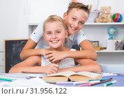 Купить «Boy is helping girl doing homework», фото № 31956122, снято 12 июля 2020 г. (c) Яков Филимонов / Фотобанк Лори