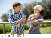 country couple of farmers drink milk in field near fenc. Стоковое фото, фотограф Татьяна Яцевич / Фотобанк Лори