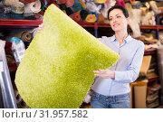 Купить «Young woman customer choosing colored carpet», фото № 31957582, снято 22 ноября 2017 г. (c) Яков Филимонов / Фотобанк Лори