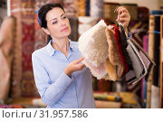 Купить «Adult woman shopping carpet and showing samples», фото № 31957586, снято 22 ноября 2017 г. (c) Яков Филимонов / Фотобанк Лори