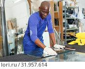 Купить «Glazier working in glass factory», фото № 31957614, снято 16 мая 2018 г. (c) Яков Филимонов / Фотобанк Лори