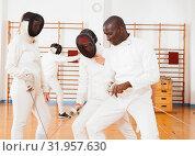 Купить «woman fencer practicing new movements with trainer at fencing room», фото № 31957630, снято 11 июля 2018 г. (c) Яков Филимонов / Фотобанк Лори