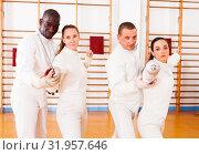 Купить «Men and women fencers posing with foils together at fencing workout», фото № 31957646, снято 11 июля 2018 г. (c) Яков Филимонов / Фотобанк Лори