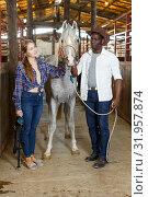 Купить «Man and girl posing near horse», фото № 31957874, снято 2 октября 2018 г. (c) Яков Филимонов / Фотобанк Лори