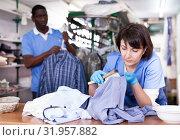 Купить «Female laundry worker during daily work», фото № 31957882, снято 15 января 2019 г. (c) Яков Филимонов / Фотобанк Лори