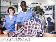 Купить «Workers of laundry showing clean clothing», фото № 31957902, снято 15 января 2019 г. (c) Яков Филимонов / Фотобанк Лори