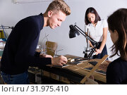 Купить «Student engaged in architectural modeling with groupmates», фото № 31975410, снято 8 ноября 2018 г. (c) Яков Филимонов / Фотобанк Лори