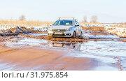 Купить «Russia, Samara, March 2019: A passenger car overcomes a muddy puddle in the spring thaw on a country road.», фото № 31975854, снято 30 марта 2019 г. (c) Акиньшин Владимир / Фотобанк Лори