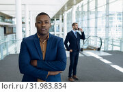 Купить «Two businessmen standing in the lobby of a modern business building», фото № 31983834, снято 21 марта 2019 г. (c) Wavebreak Media / Фотобанк Лори