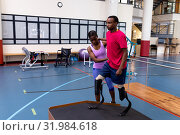 Купить «Physiotherapist helping disabled man walk with prosthetic leg on ramp in sports center», фото № 31984618, снято 24 марта 2019 г. (c) Wavebreak Media / Фотобанк Лори