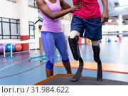Купить «Female physiotherapist helping disabled man walk with prosthetic leg on ramp in sports center», фото № 31984622, снято 24 марта 2019 г. (c) Wavebreak Media / Фотобанк Лори