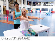 Trainer assisting disabled active senior woman to exercise in sports center. Стоковое фото, агентство Wavebreak Media / Фотобанк Лори