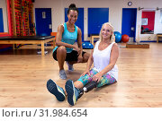 Female trainer and disabled active senior woman looking at camera in sports center. Стоковое фото, агентство Wavebreak Media / Фотобанк Лори