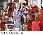 Купить «Attentive man carefully examining antiques», фото № 31985446, снято 15 мая 2018 г. (c) Яков Филимонов / Фотобанк Лори