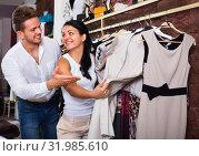 Купить «Family choosing dress and blouse at clothing shop», фото № 31985610, снято 24 октября 2016 г. (c) Яков Филимонов / Фотобанк Лори