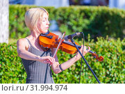 Купить «Russia, Samara, June 2019. Young violinist playing in the park.», фото № 31994974, снято 9 июня 2019 г. (c) Акиньшин Владимир / Фотобанк Лори