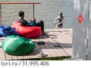 Купить «Девушка на вейкборде подъезжает к причалу. На причале в кресле-мешке сидит спортсмен, управляющий канатной тягой», фото № 31995406, снято 28 июля 2019 г. (c) Наталья Николаева / Фотобанк Лори