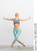 Купить «Fit sporty active girl in fashion sportswear doing yoga fitness exercise in front of gray wall, outdoor sports, urban style», фото № 32003210, снято 24 мая 2019 г. (c) Matej Kastelic / Фотобанк Лори
