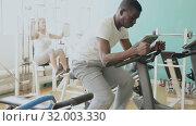 Купить «Group of people exercising with weight and on simulators in gym», видеоролик № 32003330, снято 24 марта 2019 г. (c) Яков Филимонов / Фотобанк Лори