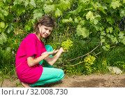 Купить «Девочка в саду с виноградом. Август», фото № 32008730, снято 8 августа 2019 г. (c) Александр Романов / Фотобанк Лори