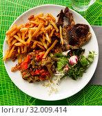 Купить «Portion of barbecued lamb ribs with french fries and vegetable garnish», фото № 32009414, снято 21 сентября 2019 г. (c) Яков Филимонов / Фотобанк Лори