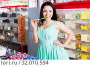 Купить «Woman posing to photographer with lollypop», фото № 32010594, снято 25 апреля 2017 г. (c) Яков Филимонов / Фотобанк Лори