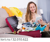 Купить «Smiling woman sitting on sofa and packing suitcase», фото № 32010622, снято 21 марта 2017 г. (c) Яков Филимонов / Фотобанк Лори