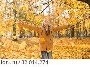 Купить «Счастливая девочка бросает вверх разноцветные опавшие листья в осеннем парке», фото № 32014274, снято 14 октября 2018 г. (c) Лариса Капусткина / Фотобанк Лори