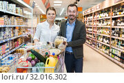 Couple is standing with trolley with food in supermarket. Стоковое фото, фотограф Яков Филимонов / Фотобанк Лори