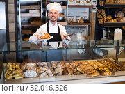 Купить «Young guy baker is offering fresh tasty croissant», фото № 32016326, снято 26 января 2017 г. (c) Яков Филимонов / Фотобанк Лори