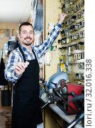 Купить «male worker showing key he made in repair workshop», фото № 32016338, снято 2 февраля 2017 г. (c) Яков Филимонов / Фотобанк Лори