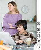Son plaing video games at laptop, sad mom on background. Стоковое фото, фотограф Яков Филимонов / Фотобанк Лори