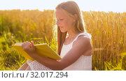 Купить «smiling young girl reading book on cereal field», видеоролик № 32017294, снято 4 августа 2019 г. (c) Syda Productions / Фотобанк Лори