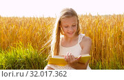 Купить «smiling young girl reading book on cereal field», видеоролик № 32017362, снято 4 августа 2019 г. (c) Syda Productions / Фотобанк Лори