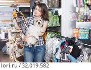 Купить «Adult woman holding dog and choosing clothes», фото № 32019582, снято 7 мая 2018 г. (c) Яков Филимонов / Фотобанк Лори
