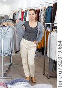 Купить «Woman trying blouse clothing boutique», фото № 32019654, снято 10 октября 2018 г. (c) Яков Филимонов / Фотобанк Лори