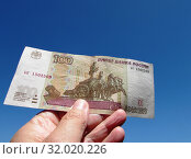 Купюра сто рублей на синем небе. Стоковое фото, фотограф Татьяна Матвейчук / Фотобанк Лори