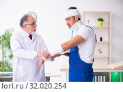 Young male contractor visiting old doctor. Стоковое фото, фотограф Elnur / Фотобанк Лори