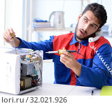 Купить «Young repairman fixing and repairing microwave oven», фото № 32021926, снято 11 июля 2017 г. (c) Elnur / Фотобанк Лори