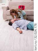 Купить «Young couple in first aid concept at home», фото № 32024178, снято 10 мая 2019 г. (c) Elnur / Фотобанк Лори