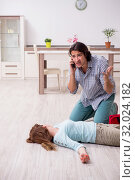Купить «Young couple in first aid concept at home», фото № 32024182, снято 10 мая 2019 г. (c) Elnur / Фотобанк Лори