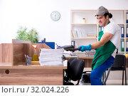 Купить «Young handsome contractor cleaning the office», фото № 32024226, снято 9 мая 2019 г. (c) Elnur / Фотобанк Лори