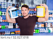 Купить «Young sporty man standing in store, holding big cans of sport nutrition», фото № 32027018, снято 12 апреля 2018 г. (c) Яков Филимонов / Фотобанк Лори